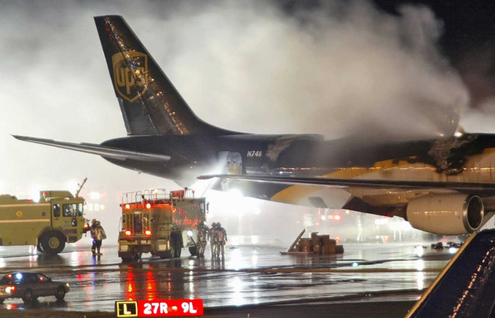 FILE - In this Feb. 8, 2006 file photo, firefighters battle a blaze onboard a UPS cargo plane at Philadelphia International Airport in Philadelphia. New U.S. government tests are raising concern that rechargeable lithium batteries carried as cargo on passenger airliners around the world are susceptible to fires or explosions that could destroy the planes. Yet U.S. and international officials have been slow to adopt safety restrictions that might affect both powerful industries that depend on the batteries and the airlines that profit from shipping them. The batteries are for products ranging from cellphones and laptops to hybrid cars. (AP Photo/Joseph Kaczmarek, File)